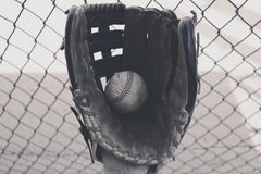 Old baseball in glove with dugout fence Stock Photos