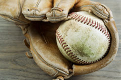 Old Baseball and Glove on Faded Wood Stock Photography