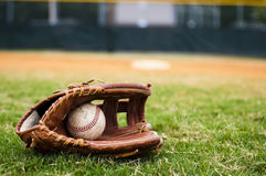 Old Baseball and Glove on Field. With base and outfield in background Royalty Free Stock Image