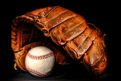 Old Baseball Glove and Professional Ball on Black Stock Images