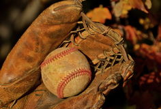Old baseball and glove. An old scuffed baseball lies in the pocket of an old glove Stock Photography