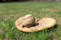 Old Baseball and Glove. View of an old fashioned baseball glove and ball on a grass outfield Royalty Free Stock Images