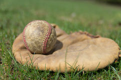Old Baseball and Glove. A vintage baseball glove with a well worn ball on a grass field Royalty Free Stock Images