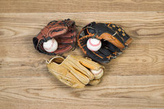 Old Baseball Gloves and balls on aged wood Stock Images
