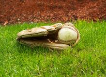 Old Baseball inside Used Glove on ground Stock Photos