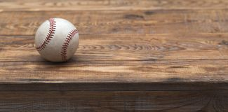 Baseball on a old rustic wooden desk with partial blur background. Old baseball left on a old rustic wooden table. Classic Rawlings ball. Partially blur Royalty Free Stock Photos