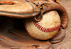 Old Baseball and Mitt. Well worn and used baseball in the pocket of a baseball mitt Royalty Free Stock Photos