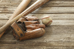 Old baseball, mitt and bats on a rough wood surface. An old baseball, mitt and wooden bats on a rough wood surface Royalty Free Stock Image