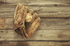 Old baseball and mitt on rough wood background. Vintage baseball mitt and ball on grungy, rough wood background viewed from above Stock Image