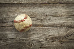 Old baseball on rough wood surface Stock Photography