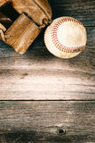 Old baseball and worn mitt on old wood with vintage style Royalty Free Stock Photo