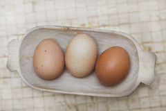 Old basket with three organic eggs. Stock Image