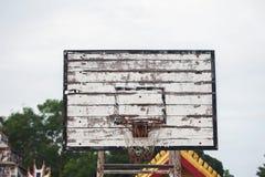 Old basketball backboard and basket. Deserted basketball backboard on a background of trees Stock Photos
