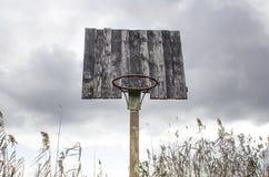 Old basketball backboard and basket. Deserted basketball backboard. On a background of trees Stock Photography