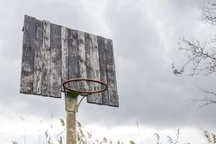 Old basketball backboard and basket. Deserted basketball backboard. On a background of trees Stock Photo