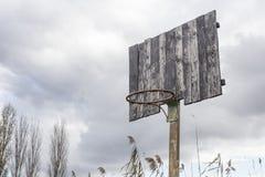 Old basketball backboard and basket. Deserted basketball backboard. On a background of trees Stock Photos