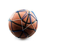 Old basketball ball in a net isolated on white background Stock Photo