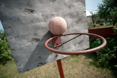 Old basketball and basket on weathered wooden facade Stock Images