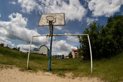 Old basketball court, basket, snatched netting against the sky Stock Photos