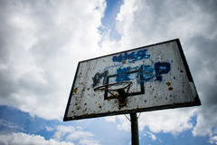 Old basketball court, basket, snatched netting against the sky Stock Image
