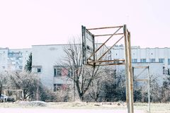 Old basketball ring on the sports ground. An old basketball court on a sports ground, next to a multistory building stock photos