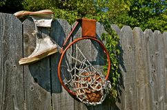 Old Basketball Equipment. An old pair of tennis shoes, rim, and basketball are hung on an weathered fence Stock Images