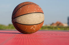 Old basketball on the ground. Old basketball ball on a outdoor court in public park Royalty Free Stock Image