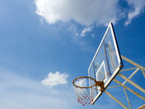 Old basketball hoop against blue sky. Old basketball hoop with backboard against  blue sky, white cloud Stock Photo