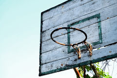 Old basketball hoop with blue sky background. Closeup of old basketball hoop with vines and blue sky background Royalty Free Stock Photo