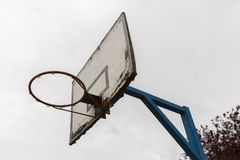 An old basketball ring with a white wooden plate where paint is peeling off and fixed to a blue steel pole on a white background Royalty Free Stock Images
