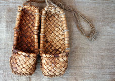 Old bast shoes traditional russian footwear on a sackcloth Stock Images