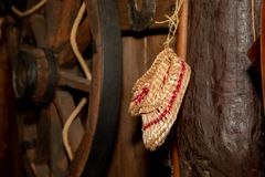 Old bast slippers hang on the background of the old wheel royalty free stock photo
