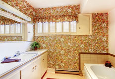 Old bathroom with floral pattern wallpaper, white cabinets and b Royalty Free Stock Photography