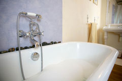 Old bathtub with foam Stock Images