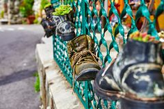 Old battered boots with lace on fence Stock Photo