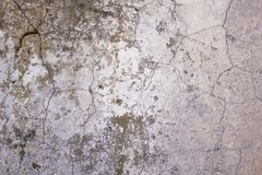 Old, battered, damaged white concrete wall with cracks and dark paint and mildew stains. rough surface texture. A old, battered, damaged white concrete wall with royalty free stock photography