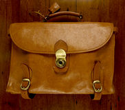 Old battered, leather  briefcase  wood background Royalty Free Stock Images