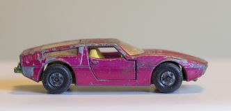 Old battered pink toy car. Side view of a small pink metal toy car Stock Photography