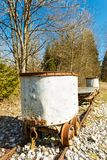 Old battered rusty bucket trolley on a rail track Royalty Free Stock Photography