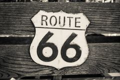 Old and battered traffic sign Route 66. On a wooden surface. Stylization. Sepia stock photography
