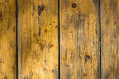 Old battered yellow gray wooden surface made of boards with scratches and dirt stains. vertical lines. rough surface texture. A old battered yellow gray wooden royalty free stock images