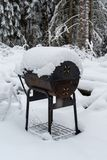 An old bbq grill covered in snow. An old bbq grill covered in white snow Royalty Free Stock Image