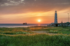 An old beacon and sunset. Stock Photos