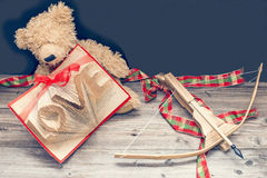 Old bear with bow and arrow. Old bear with vintage old book and bow and arrow stock photos