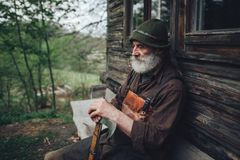 Old bearded forester with axe near wooden hut. Portrait of old bearded forester with axe near wooden hut royalty free stock photo