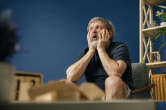 Old bearded man with alzheimer desease. Inability to tolerate. Old bearded man with alzheimer desease sitting on the chair and suffering from headache. Concept royalty free stock photos