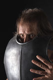 Old bearded man with breastplate and mad look. Putting on his armor Royalty Free Stock Image