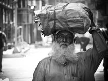 Old bearded man. Carrying load on his head Royalty Free Stock Photography