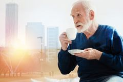 Old bearded man looking into the distance while drinking coffee Stock Photo