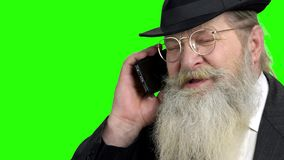 Old bearded man talking on cell phone. Serious elderly businessman negotiating on phone with client close up. Alpha Channel background stock video footage